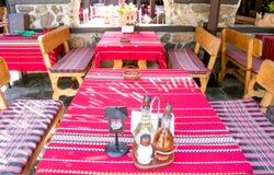 Kolorowi tradycyjni czerwoni tablecloths na drewnianych stołach i ławkach Obraz Stock