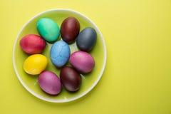 Kolorowi Wielkanocni jajka jako atrybut Wielkanocny świętowanie na koloru żółtego talerzu obraz royalty free