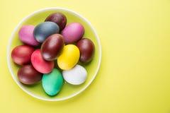 Kolorowi Wielkanocni jajka jako atrybut Wielkanocny świętowanie na koloru żółtego talerzu zdjęcie royalty free