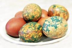 Kolorowi Wielkanocni jajka na bielu talerzu umieszczającym rozsypiskiem Obrazy Stock