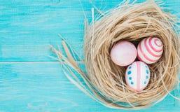 Kolorowi Wielkanocni jajka na nieociosanym drewnianym tle z gniazdową Selekcyjną ostrością Odgórny widok Zdjęcia Stock
