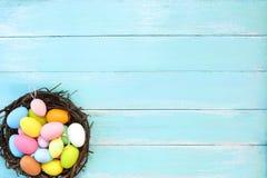 Kolorowi Wielkanocni jajka w gniazdeczku na błękitnym drewnianym tle obraz royalty free