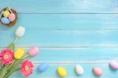 Kolorowi Wielkanocni jajka w gniazdeczku z kwiatami na błękitnym drewnianym tle fotografia stock