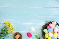 Kolorowi Wielkanocni jajka w gniazdeczku z kwiatami na błękitnym drewnianym tle zdjęcie royalty free