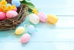 Kolorowi Wielkanocni jajka w gniazdeczku z kwiatami na błękitnym drewnianym tle zdjęcia royalty free