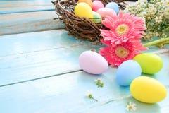 Kolorowi Wielkanocni jajka w gniazdeczku z kwiatami na błękitnym drewnianym tle zdjęcie stock
