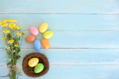 Kolorowi Wielkanocni jajka w gniazdeczku z kwiatami na błękitnym drewnianym tle obraz stock