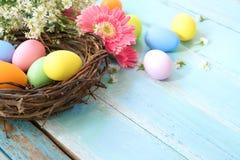 Kolorowi Wielkanocni jajka w gniazdeczku z kwiatami na błękitnym drewnianym tle obrazy stock