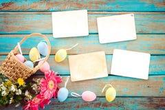 Kolorowi Wielkanocni jajka w gniazdeczku z kwiatem i pustym starym papierowym albumu fotograficznym na drewno stole Obrazy Royalty Free
