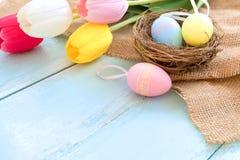Kolorowi Wielkanocni jajka w gniazdeczku z tulipanowymi kwiatami na błękitnym drewnianym tle obrazy stock