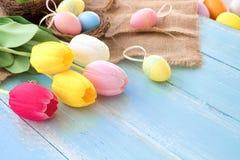 Kolorowi Wielkanocni jajka w gniazdeczku z tulipanowymi kwiatami na błękitnym drewnianym tle zdjęcia royalty free