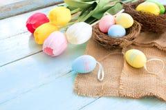 Kolorowi Wielkanocni jajka w gniazdeczku z tulipanowymi kwiatami na błękitnym drewnianym tle Obraz Stock