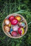 Kolorowi Wielkanocni jajka w kosza i zielonej trawy tle Zdjęcia Stock