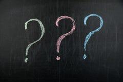 Kolorowi znak zapytania na czarnym chalkboard zdjęcia stock