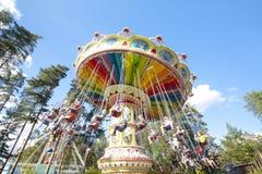 Kolorowy łańcuch huśtawki carousel w ruchu przy parkiem rozrywki na niebieskiego nieba tle Obraz Royalty Free
