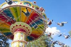 Kolorowy łańcuch huśtawki carousel w ruchu przy parkiem rozrywki na niebieskiego nieba tle Zdjęcia Royalty Free