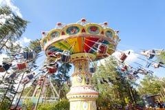 Kolorowy łańcuch huśtawki carousel w ruchu przy parkiem rozrywki na niebieskiego nieba tle Obrazy Royalty Free