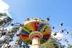 Kolorowy łańcuch huśtawki carousel w ruchu przy parkiem rozrywki na niebieskiego nieba tle Obraz Stock