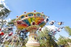 Kolorowy łańcuch huśtawki carousel w ruchu przy parkiem rozrywki na niebieskiego nieba tle Fotografia Stock