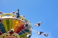 Kolorowy łańcuch huśtawki carousel w ruchu przy parkiem rozrywki na niebieskiego nieba tle Zdjęcia Stock