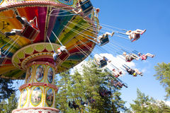 Kolorowy łańcuch huśtawki carousel w ruchu przy parkiem rozrywki na niebieskiego nieba tle Obrazy Stock