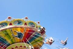 Kolorowy łańcuch huśtawki carousel w ruchu przy parkiem rozrywki na niebieskiego nieba tle Fotografia Royalty Free