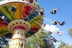 Kolorowy łańcuch huśtawki carousel w ruchu przy parkiem rozrywki na niebieskiego nieba tle Zdjęcie Royalty Free