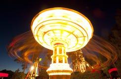Kolorowy łańcuch huśtawki carousel w ruchu przy parkiem rozrywki przy nocą zdjęcie stock
