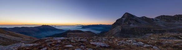 Kolorowy światło słoneczne za majestatycznymi halnymi szczytami włoszczyzna - Francuscy Alps, przeglądać od odległego Mgła i mgła obraz royalty free