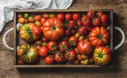 Kolorowy asortyment heirloom, wiązka i czereśniowi pomidory w nieociosanej tacy nad drewnianym tłem, Fotografia Royalty Free