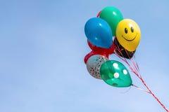 Kolorowy balonowy unosić się w w połowie powietrzu przeciw jaskrawemu niebieskiemu niebu Zdjęcia Royalty Free