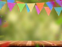 Kolorowy chorągwiany sztandar i confetti na drewno stole z plamą zieleniejemy zdjęcia stock