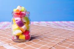 Kolorowy cukierek w słoju na stole z błękitnym tłem Zdjęcie Royalty Free