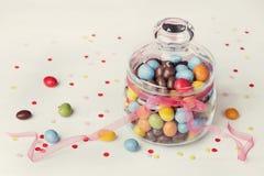 Kolorowy cukierku słój dekorował z łęku faborkiem na białym tle z confetti Fotografia Stock