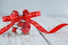 Kolorowy cukierku słój dekorujący z czerwonym łękiem z sercami na białym drewnianym tle Zdjęcia Stock