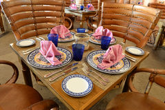 Kolorowy dinnerware na drewnianych stołach Obrazy Stock
