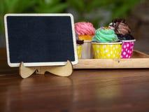 Kolorowy domowej roboty babeczka na drewnianej tacy z pustą blackboard i kopii przestrzenią dla twój teksta Zdjęcia Royalty Free