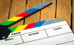 Kolorowy filmu clapboard lying on the beach na drewnianej powierzchni jak widzieć od above fotografia stock