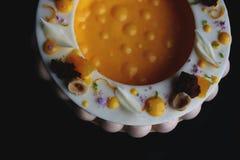 Kolorowy galanteryjny pomarańcze i hazelnut cheesecake odizolowywający na czarnym tle obrazy stock