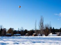 Kolorowy gorące powietrze balonu latanie nad śnieg zakrywał pole Zdjęcia Royalty Free