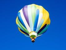 Kolorowy gorące powietrze balonu latanie w jaskrawym niebieskim niebie Obraz Royalty Free