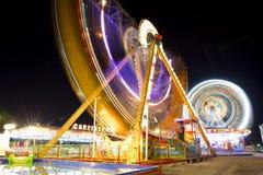 Kolorowy karnawałowy Ferris gondoli i koła przędzalnictwo w ruchu zamazywał przy nocą Obraz Royalty Free