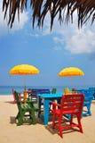 Kolorowy krzesło i stół z żółtym parasolem na plaży Fotografia Stock