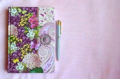 Kolorowy kwiecisty notatnik na świetle - różowy jedwabniczy tło z kopii przestrzenią Fotografia Royalty Free