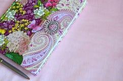 Kolorowy kwiecisty notatnik na świetle - różowy jedwabniczy tło z kopii przestrzenią Zdjęcie Stock