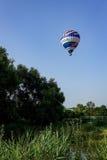 Kolorowy lotniczy balon lata nad miast przedmieściami Zdjęcie Royalty Free