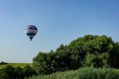 Kolorowy lotniczy balon lata nad miast przedmieściami Obrazy Royalty Free