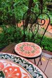 Kolorowy malujący kamienny krzesło przy tarasową zielenią w ogródzie Obrazy Stock