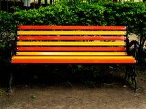 Kolorowy opróżnia ławkę w ogródzie zdjęcie stock