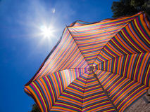 Kolorowy pasiasty parasol przeciw niebu i słońcu gorąca pogoda Plażowy wakacje Zdjęcie Royalty Free